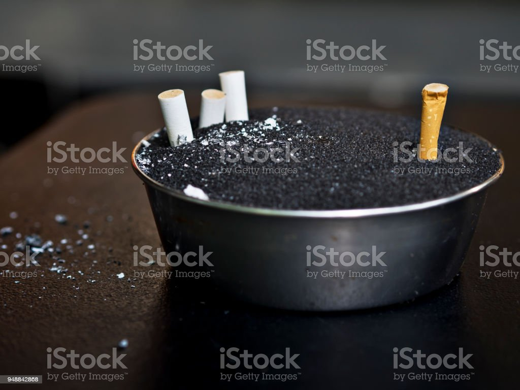 Smoking area with cigarettes and cigarette scraps in ashtray on wooden table, dirty and smoke for health, lung cancer concept copy space and background stock photo