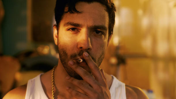 Smoking Brutal Gang Member with Gold Chain Looks into Camera with Defiance. Underground Drug Laboratory is in Background. Smoking Brutal Gang Member with Gold Chain Looks into Camera with Defiance. Underground Drug Laboratory is in Background. drug cartel stock pictures, royalty-free photos & images