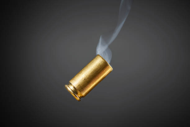 smoking bullet casing - proiettile foto e immagini stock