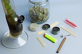 istock Smoking cannabis accessories and stuff on gray background. Bong, blunt and joint paper, grinder and marijuana buds in jar 1267508580