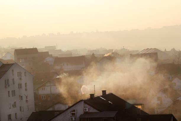 Chaminés em telhados de casas a fumar emite fumaça, poluição atmosférica ao nascer do sol, poluentes digite atmosfera. Desastre ambiental. As emissões nocivas e os gases de escape para a atmosfera. Neblina, dia de inverno, a estação de aquecimento. - foto de acervo
