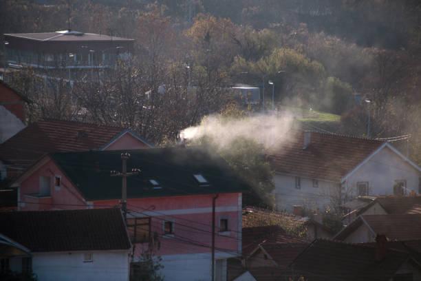 As chaminés de fumo em telhados das casas emitem o fumo, a poluição atmosférica no nascer do sol, os poluentes entram a atmosfera. Desastre ambiental. Emissões nocivas e gases de escape no ar. Nevoeiro, dia de inverno, estação de aquecimento. - foto de acervo