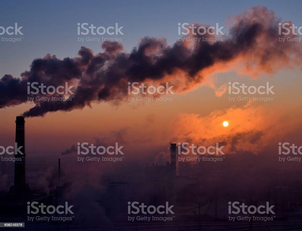 Smoking chimneys at sunrise stock photo
