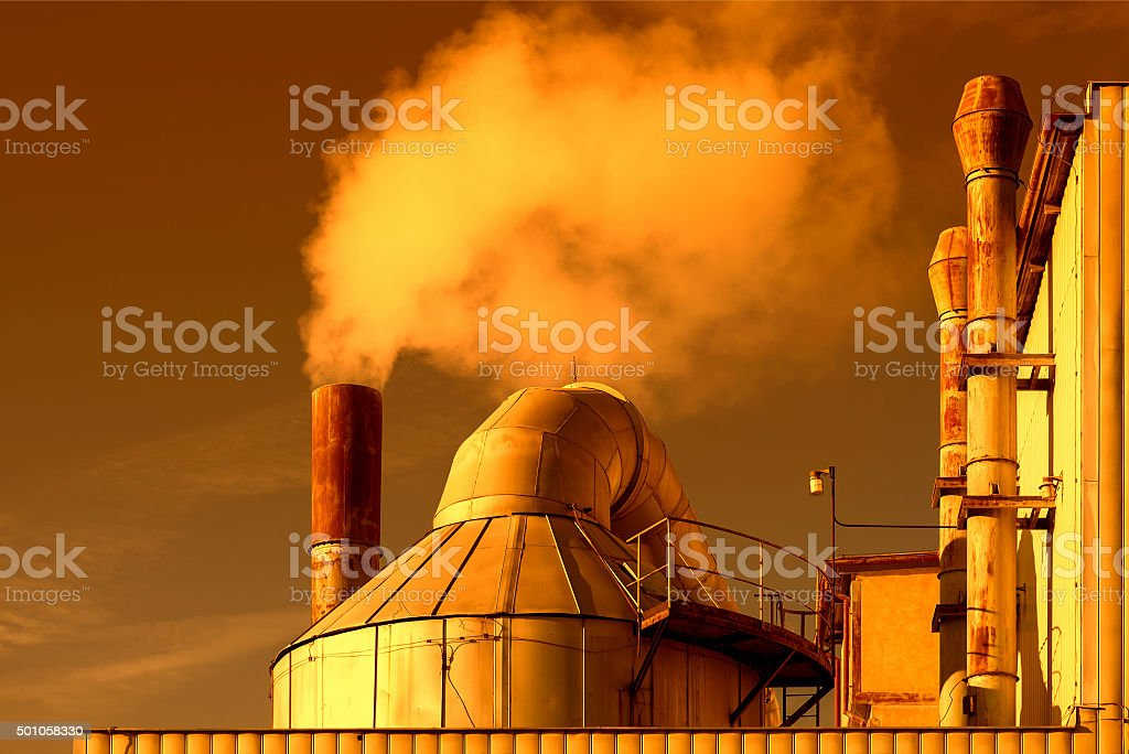 Smoking chimneys of a factory in the sunset stock photo