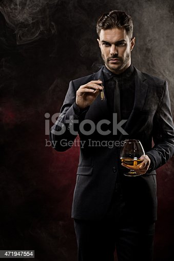 471947536 istock photo smoking cigar and drinking whiskey well dressed man 471947554