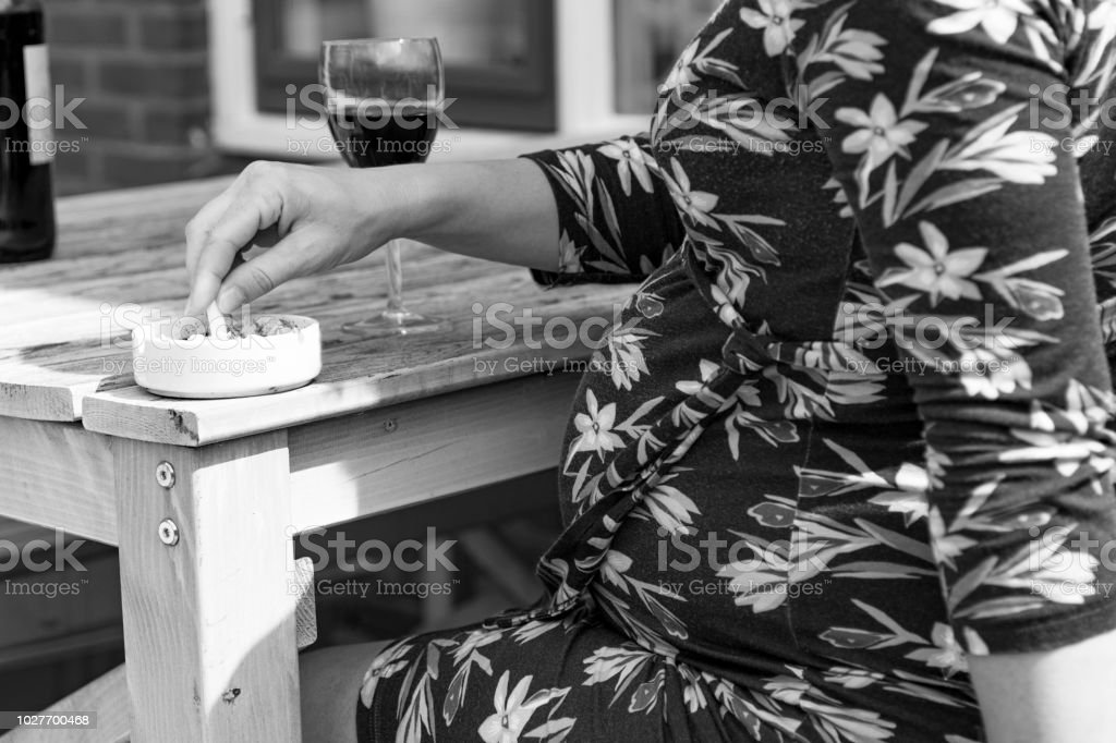 Smoking cigarettes and drinking while pregnant stock photo