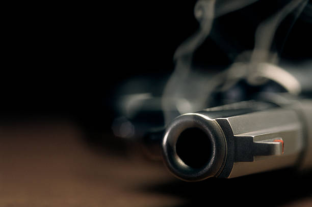 Smoking gun lying on the floor, revolver A gritty crime scene image of a smoking hand gun, revolver, lying on the floor with narrow focus on the tip if the barrel and dark background pistol stock pictures, royalty-free photos & images