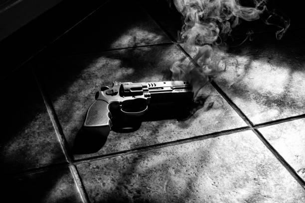 smoking gun on the foor - murder mystery stock photos and pictures
