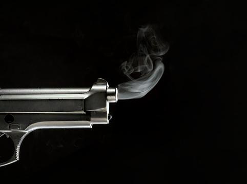 Profile of smoking gun releasing smoke from the gun barrel