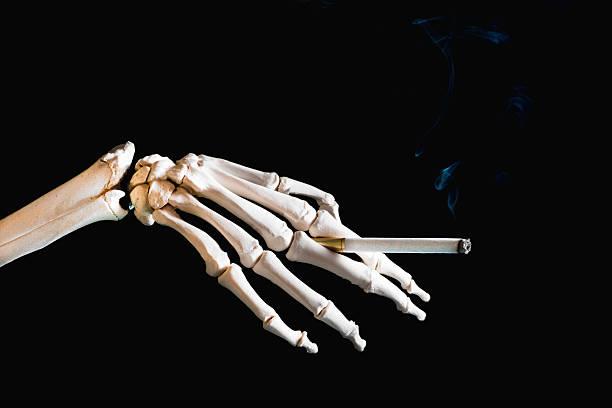 rauchen ist tödlich - skelett hand stock-fotos und bilder
