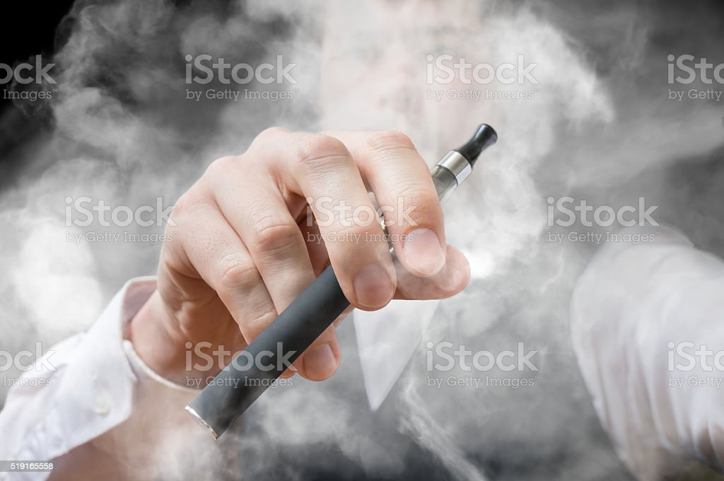 Smoking man holds electronic cigarette. A lot of smoke. stock photo