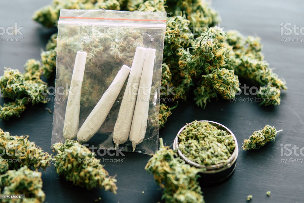 smoking marijuana, dark background close up, top view rolled jamb joint in the hands of a man marijuana weed and grinder for weed, concepts of stock photo