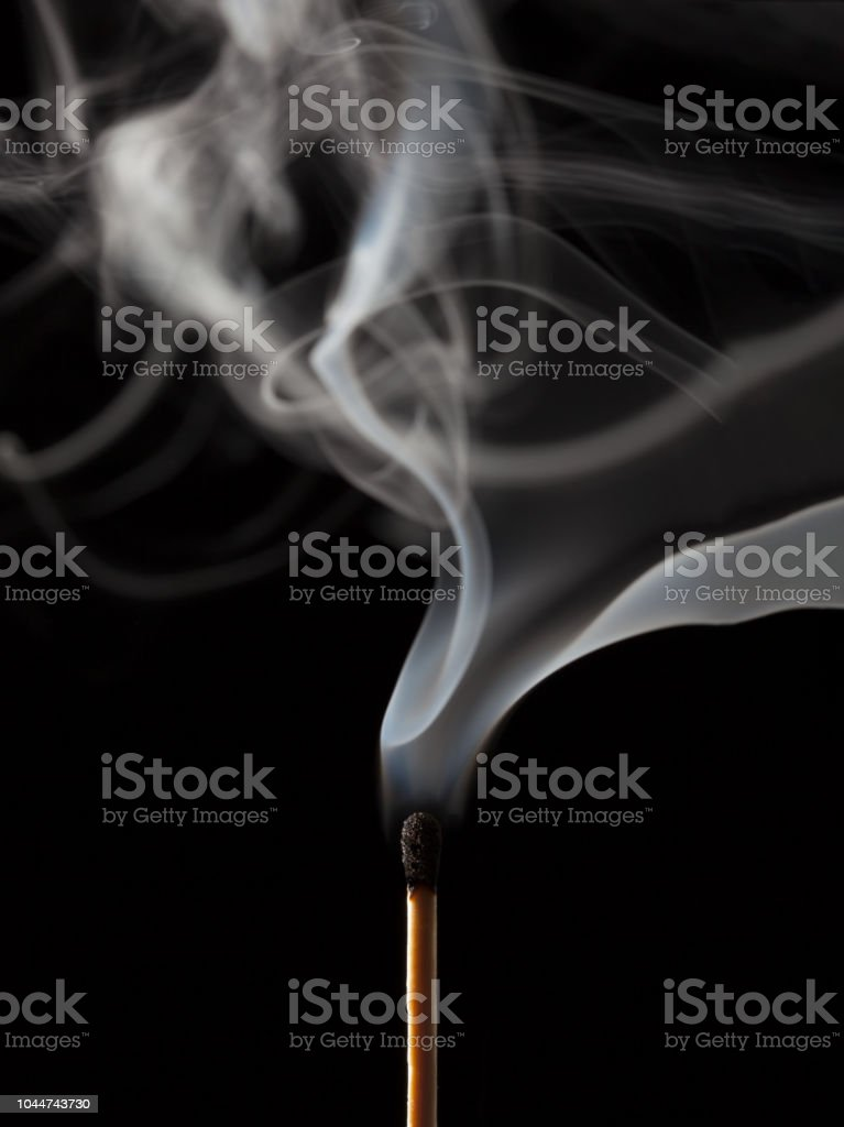 Smoking matchstick, just extinguished, on dark background - fotografia de stock