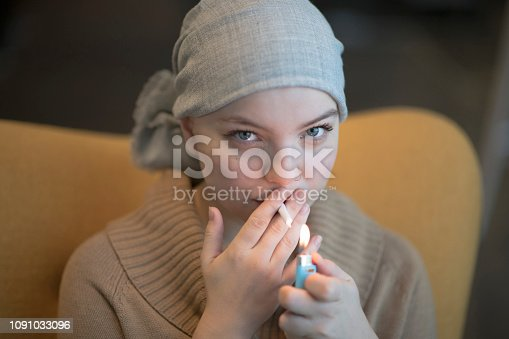 A young female is wearing a light grey headscarf. She is lighting up medical marijuana and using it for pain treatment as she has cancer. She is sitting in her lounge room and is in the comfort of her own home.