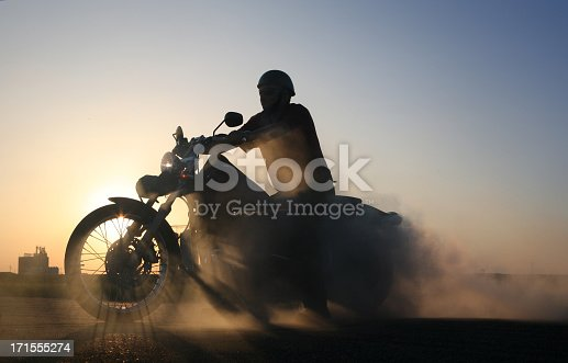 Silhouette of motorcycle and rider against blue prairie sky. Sunlight casts gorgeous shadows through wheel spokes, while smoke from burning tire billows behind bike