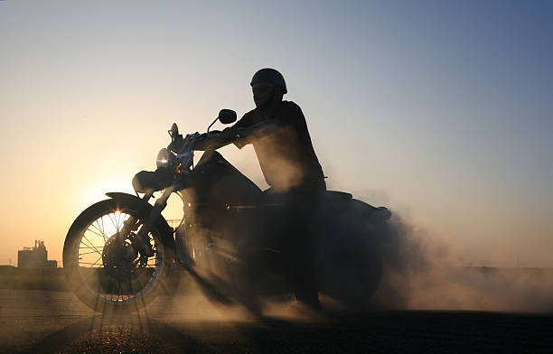 smoking motorbike and rider sillhouetted against blue prairie sky - motorcycle stock photos and pictures