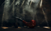 Smoking pipe cherry tree material on rusty steel background with tobacco smoke and rays of light