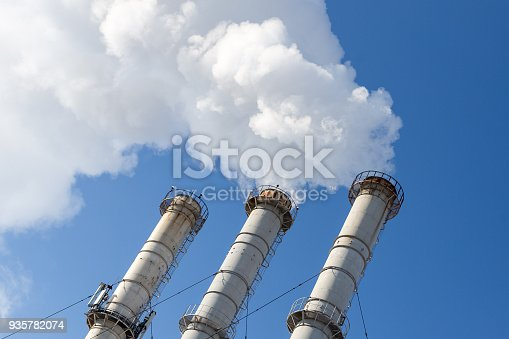 istock Smoking pipes making clouds against blue sky background. Dioxide air contamination. Environmental pollution 935782074