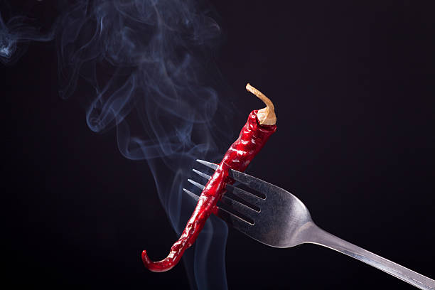 Smoking Red Hot Chilli Pepper on a black. Fork impale. – zdjęcie