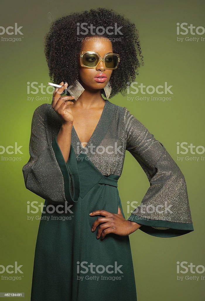 Smoking retro 70s fashion afro woman with green dress. stock photo