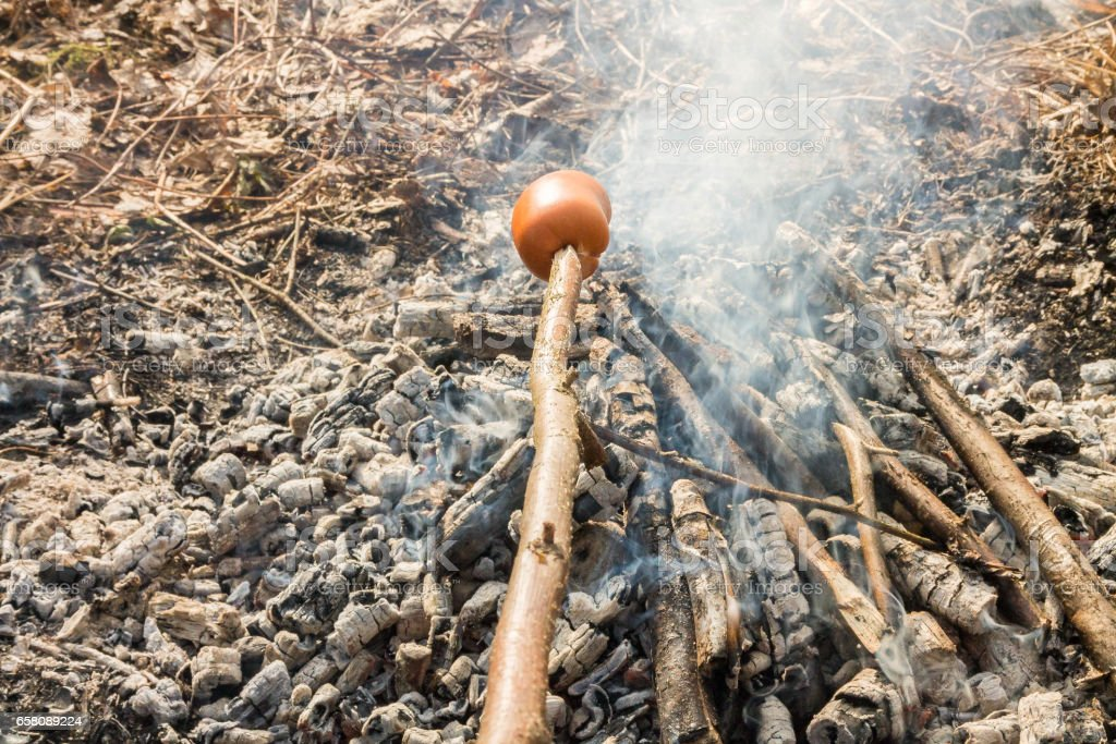Smoking sausages on the smoke. Sausages over the coals, heat. royalty-free stock photo