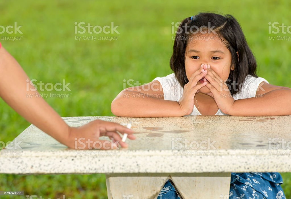 smoking that public park endangers the health of the child. stock photo