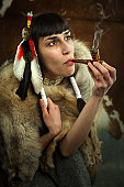 Native american woman smoking a pipe. Young beautiful woman in native american costume with wolf fur and peace pipe
