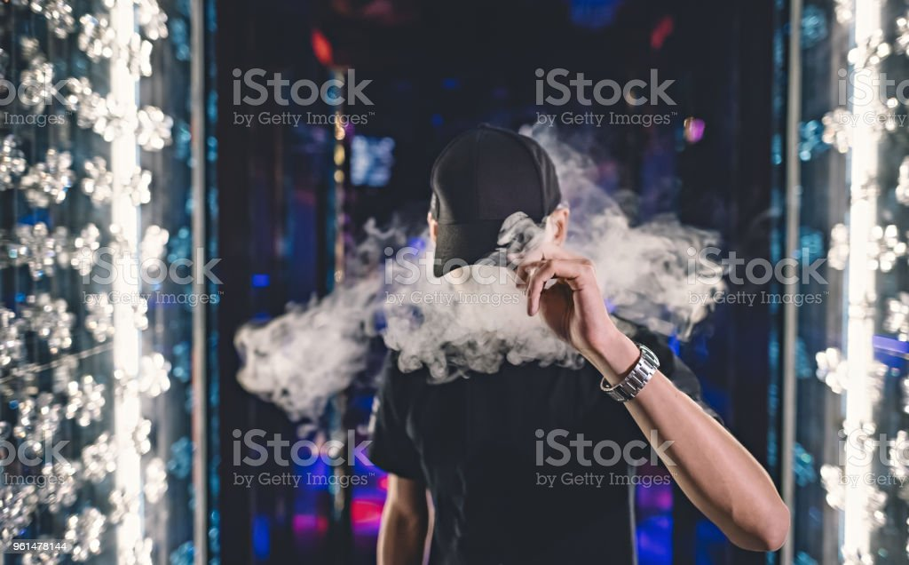 Smoking Vape Asian Chinese Male covered by hat stock photo