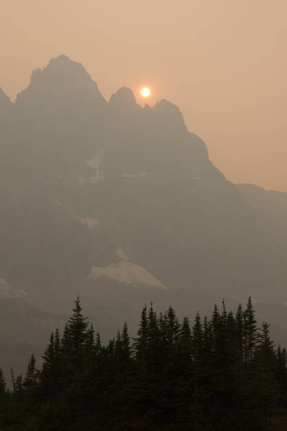 An orange sun sinks towards the Ramparts in a smoky sky filled with smoke from British Columbia wildfires.