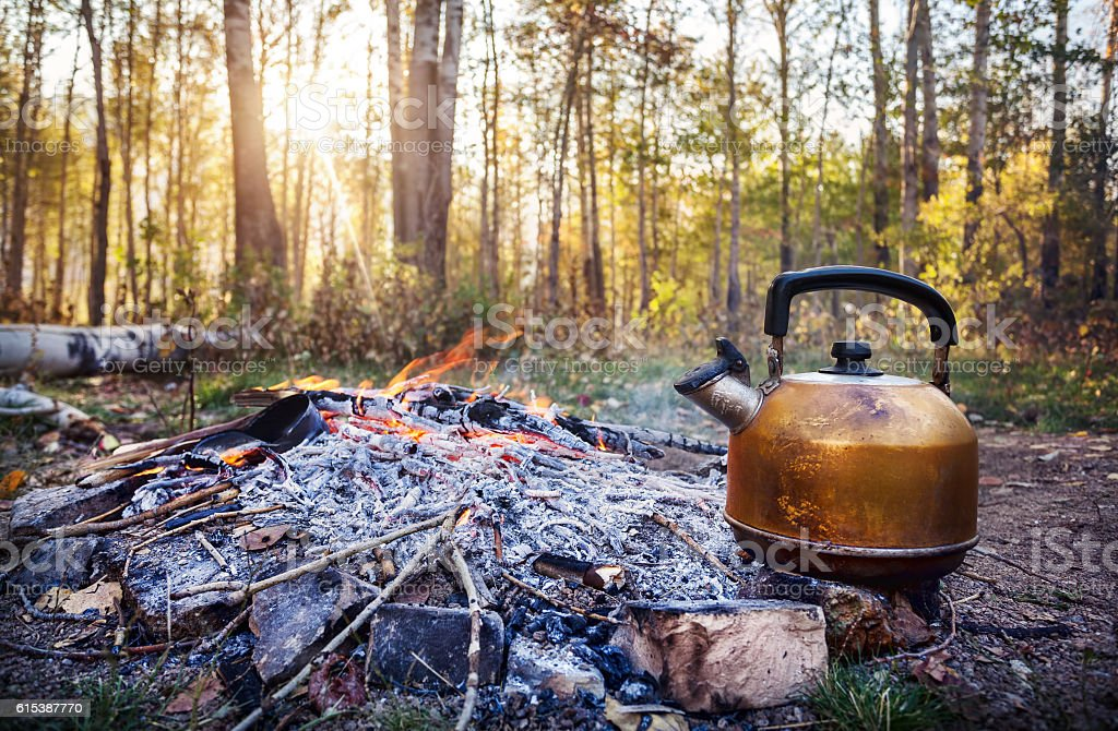 Smoky tourist tea pot on fire in morning forest stock photo