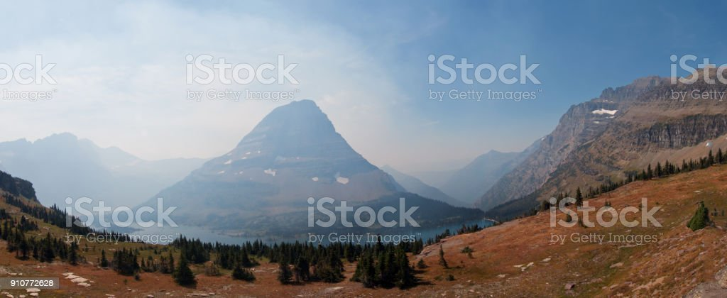 Smoky view of Bearhat Mountain seen from Hidden Lake hiking trail overlook in Glacier National Park duirng the 2017 fall fires in Montana United States stock photo