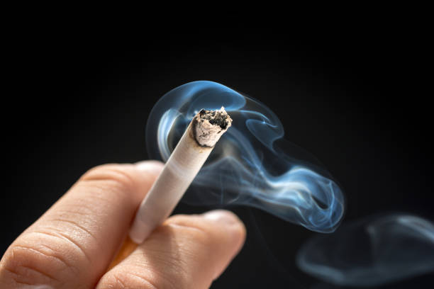 Smoldering cigarette in male hand smoking issues nicotine stock pictures, royalty-free photos & images
