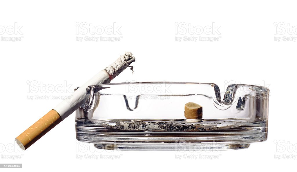 Smoldering cigarette propped against clear glass ashtray royalty-free stock photo