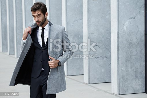Smooth businessman in coat, looking away