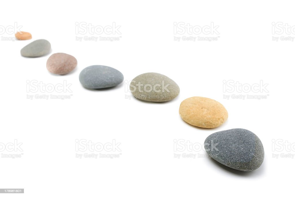 Smooth colored flat stones lined up on white background stock photo