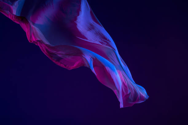 Smooth elegant transparent blue cloth separated on blue background Smooth elegant transparent blue cloth isolated or separated on dark blue studio background. Texture of flying silk fabric. floating fabric stock pictures, royalty-free photos & images