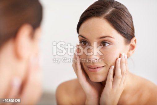 A gorgeous young woman looking at her reflection in the mirror with her hands on her face