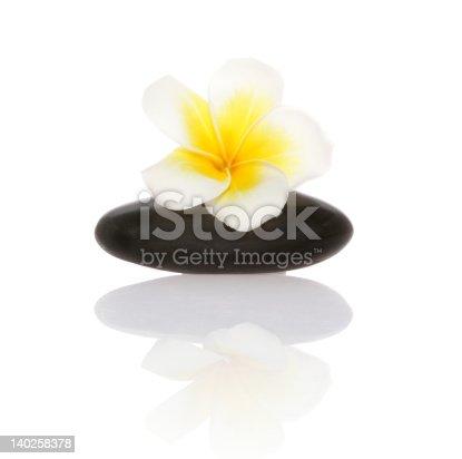 1175869940 istock photo smooth pebble and frangipani flower 140258378