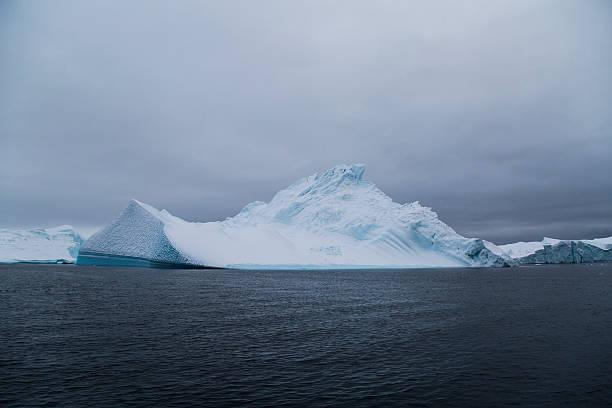 smooth snow covered iceberg stock photo