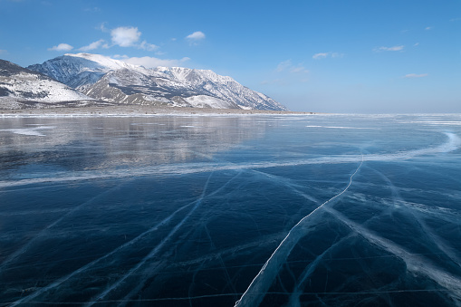 Glossy smooth surface with cracks of frozen blue ice field of lake Baikal, winter landscape