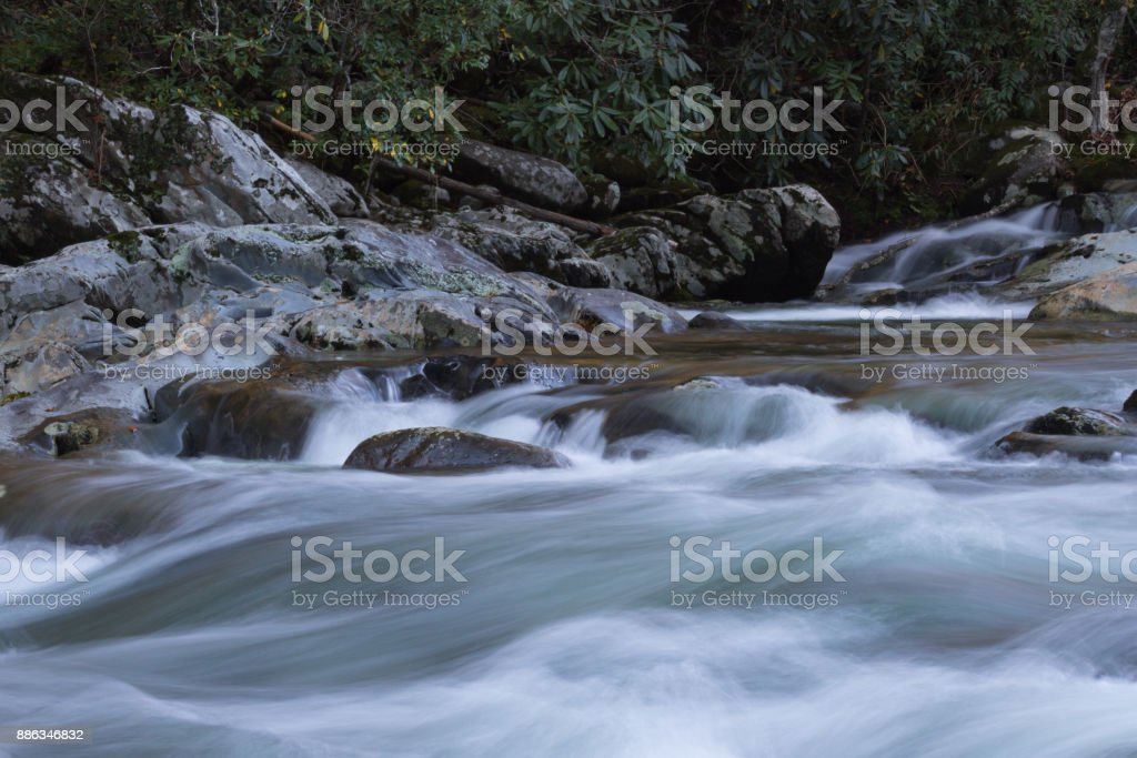 Smooth water cascade across rocks in a fast moving stream bordered by rhododendrons stock photo