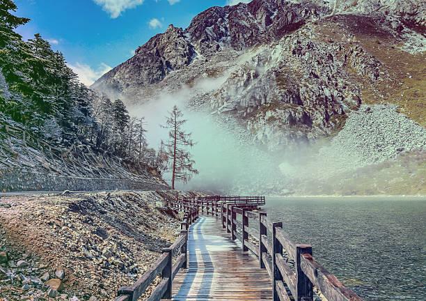 wooden bridge near smooth water of mugecuo lakes china landscape - ganzi tibet özerk bölgesi stok fotoğraflar ve resimler