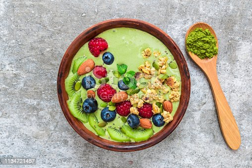istock Smoothie bowl made of matcha green tea with fresh berries, nuts, seeds with a spoon for healthy vegan breakfast 1134721457