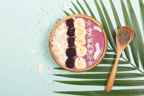 Smoothie bowl on mint background Smoothie or asai bowl on mint color background. Decorated with berries, bananas, oatmeal, dragon fruit stars, chia seeds. Minimal composition. Healthy breakfast concept. Flat lat, top view. pitaya stock pictures, royalty-free photos & images
