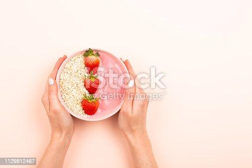 857575080istockphoto Smoothie bowl on pink background 1129812467