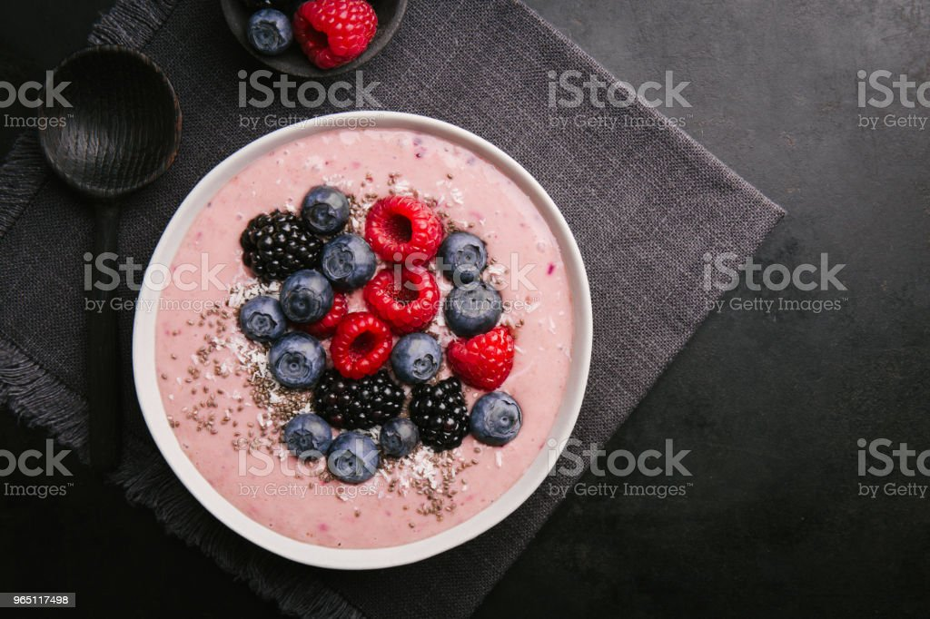 Smoothie bowl on white plate on dark background royalty-free stock photo