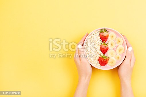 857575080istockphoto Smoothie bowl on yellow background 1129812488