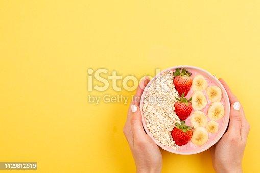857575080istockphoto Smoothie bowl on yellow background 1129812519