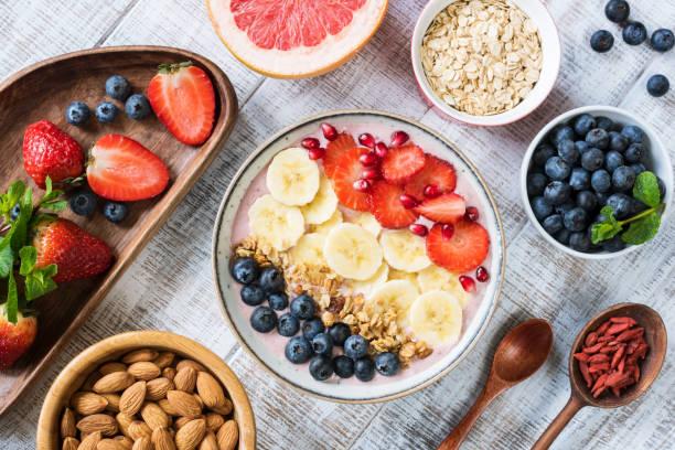 recipiente de batido con plátano, fresa, arándano, granola y granada - desayuno fotografías e imágenes de stock