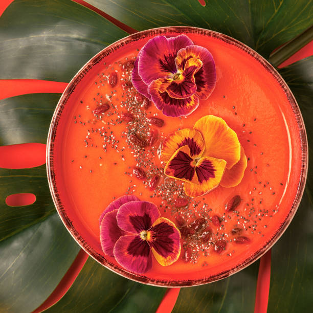 Smoothie bowl with edible pansy flowers, chia seeds, goji berries. Smoothie bowl with edible pansy flowers, chia seeds, goji berries, top view. papaya smoothie stock pictures, royalty-free photos & images